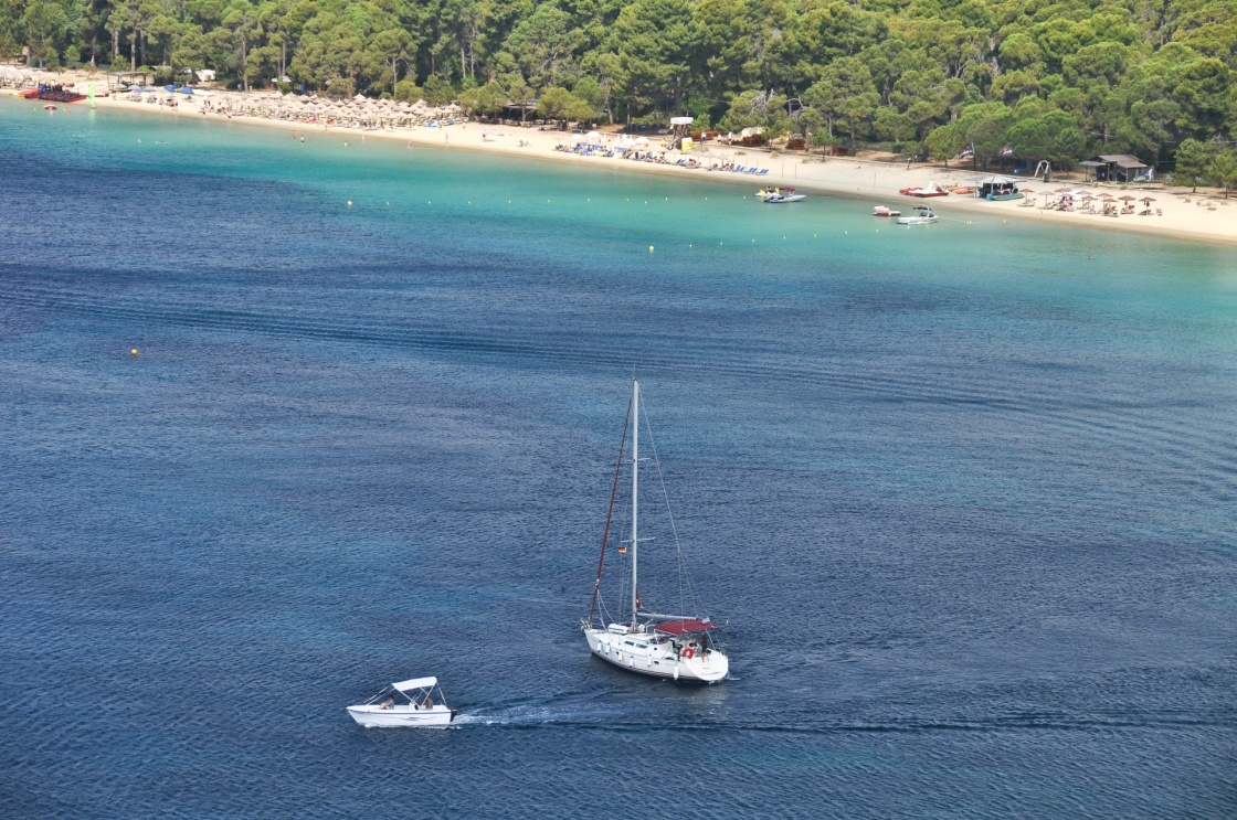 Kanapitsa Beach with sunbathers, sailboats and speedboats in a deep blue Aegean sea.